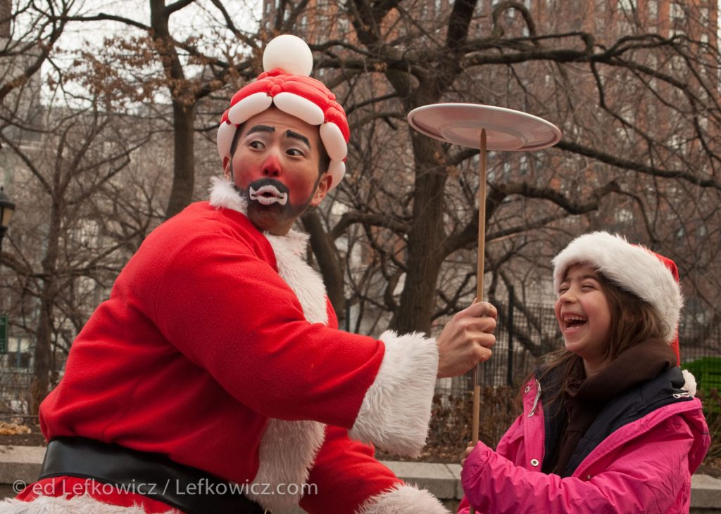 A juggling Asian Santa in Union Square helping a girl spin a plate on a stick.
